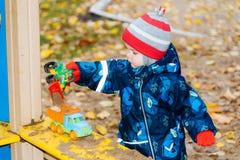 Het kind speelt auto's op de speelplaats Royalty-vrije Stock Afbeelding