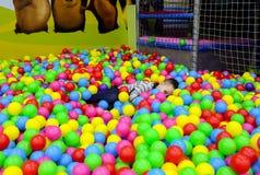 Het kind speelt in balkuil met kleurrijke plastic ballen in het centrum van het kinderenvermaak Pool met heldere ballenachtergron stock fotografie