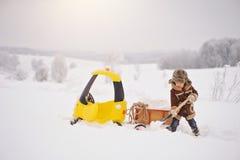 Het kind speelt buiten in de sneeuwwinter stock foto's