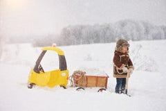Het kind speelt buiten in de sneeuwwinter stock fotografie