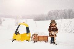 Het kind speelt buiten in de sneeuwwinter stock afbeeldingen