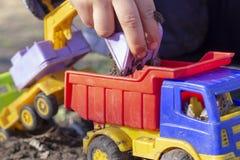 Het kind speelt in de straat met zand; hij laadt de aarde in een stuk speelgoed van de stortplaatsvrachtwagen stock foto