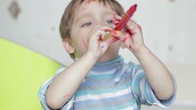 Het kind speelt met een viltpen Het gezicht van een gelukkig die kind, met een viltpen wordt geschilderd Een vuile kindlach en stock videobeelden