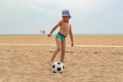 Het kind speelt voetbal op het strand stock afbeeldingen