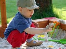 Het kind speelt in zandbak Royalty-vrije Stock Foto's