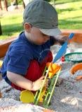 Het kind speelt in zandbak Stock Foto's