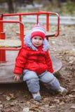 het kind spint op een schommeling in de speelplaats in het park Stock Afbeelding