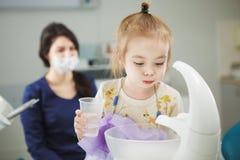 Het kind spoelt uit mond en zit als tandartsvoorzitter Royalty-vrije Stock Fotografie
