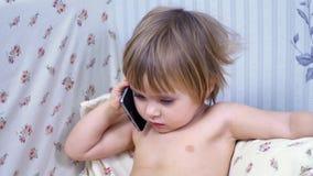 Het kind spreekt op smartphone stock videobeelden