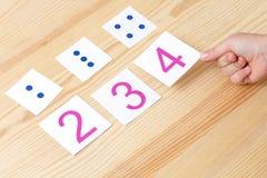 Het kind spreidt kaarten met aantallen aan kaarten met punten uit De studie van aantallen en wiskunde Royalty-vrije Stock Foto's