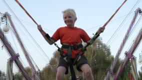 Het kind springt op een trampoline hoog omhoog tegen de hemel stock footage