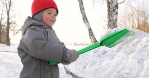 Het kind toont sneeuw groene schop stock footage