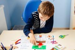 Het kind trekt een pastel van zijn leraar in schoolklasse Royalty-vrije Stock Afbeeldingen