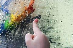 Het kind, trekt een vinger op glas stock foto