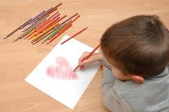 Het kind trekt hart op papier Stock Afbeeldingen