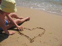 Het kind trekt hart op strand Stock Afbeeldingen