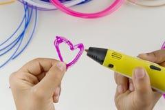 Het kind trekt met 3D pen Kleurrijke gloeidraden en witte achtergrond Royalty-vrije Stock Foto's