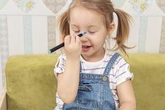 Het kind trekt op zijn neus royalty-vrije stock afbeeldingen