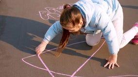 Het kind trekt in het park Het meisje trekt krijt op het asfalt stock footage