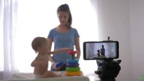 Het kind van de blogopvoeding, jonge moeder blogger met kind speelt het ontwikkelen van speelgoed terwijl het registreren van lev stock footage