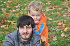 Het kind van de herfst met vader stock afbeelding