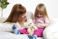 Het kind van de moeder bij bedtijd Stock Fotografie