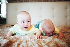 Het Kind van de zuigelingsbaby brengt thuis Broers samen Zes Maanden oud op het Bed Stock Foto