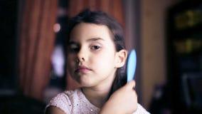 Het kind van het tienermeisje maakt haar recht kamt haar haar stock video