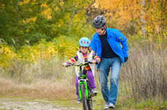 Het kind van het vaderonderwijs om fiets te berijden Royalty-vrije Stock Foto