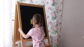 Het kind veegt een voddentekening met een zwarte raad af stock videobeelden