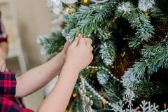 Het kind verfraait een Kerstboom Royalty-vrije Stock Afbeeldingen
