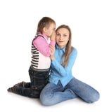 Het kind vertelt het oor van haar moeder Royalty-vrije Stock Afbeeldingen