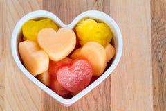 Het kind vriendschappelijke behandelt gezond van de valentijnskaartendag met hart-vormig fruit Stock Fotografie