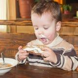 Het kind was bevuild terwijl het eten Het kind eet Een weinig stock afbeelding