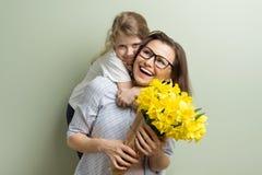 Het kind wenst moeder geluk en geeft haar boeket royalty-vrije stock foto