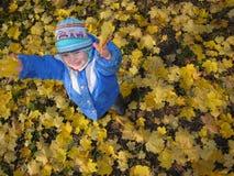 Het kind werpt bladeren Stock Fotografie