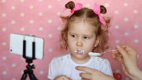 Het kind wil niet aan het eten van yoghurt De moeder probeert om de baby met kwark te voeden Het meisje kijkt stock videobeelden