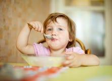 Het kind zelf eet met lepel Stock Afbeeldingen