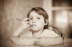 Het kind zelf eet van plaat Stock Afbeeldingen