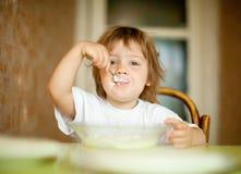 Het kind zelf eet zuivelfabriek met lepel Royalty-vrije Stock Afbeeldingen