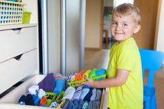 Het kind zet zijn kleren aan De jongen trekt de T-shirt uit royalty-vrije stock fotografie