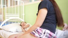 Het kind is zieke mammamedelijden de baby ziek jong geitje in bed met een thermometer de moeder naast een zieke dochter, het kind stock video