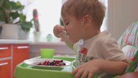 Het kind zit bij de lijst en eet een lepel verse bessen Nuttig en gezond voedsel Stock Fotografie