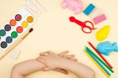 Het kind zit bij de lijst met voorwerpen voor creativiteit, tekening en hobbys, de hoogste mening stock foto's
