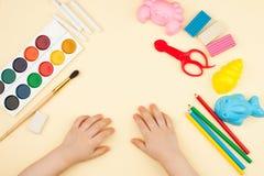Het kind zit bij de lijst met voorwerpen voor creativiteit, tekening en hobbys, de hoogste mening royalty-vrije stock afbeeldingen
