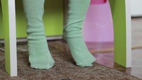 Het kind zit bij een lijst voor kinderen, beweegt zijn voeten gekleed in nylonkousen op de vloer In het kader, slechts de benen o stock videobeelden