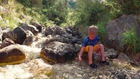 Het kind zit door de beek op de rotsen in aard stock video