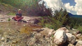Het kind zit door de beek op de rotsen in aard stock videobeelden