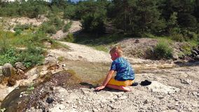 Het kind zit door de beek op de rotsen in aard stock footage