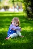 Het kind zit in een gras Royalty-vrije Stock Afbeelding